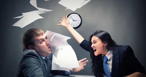 Angry business woman throwing papers in coworkers face
