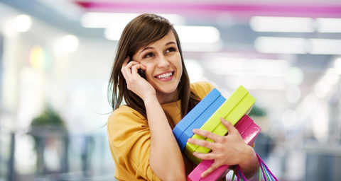 Smiling woman on phone holding multiple boxes and bags