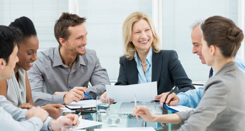 group of smiling business women and men in a meeting
