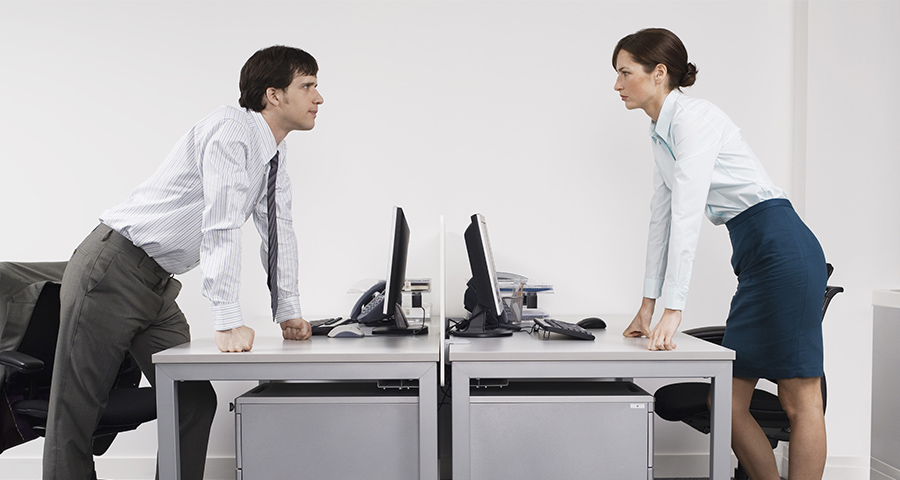 man and woman face off over their desks