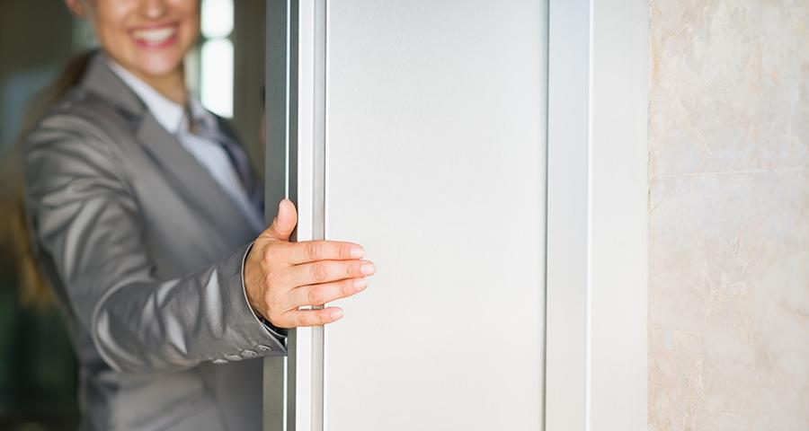 Business woman smiling in door way