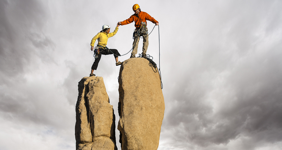man and woman climbing to top of rock