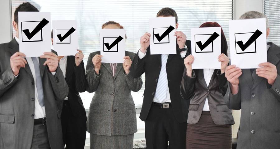 business men and women holding up signs with check mark boxes on them