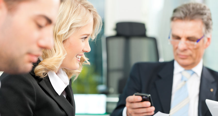 business man on phone during business meeting with another woman and man
