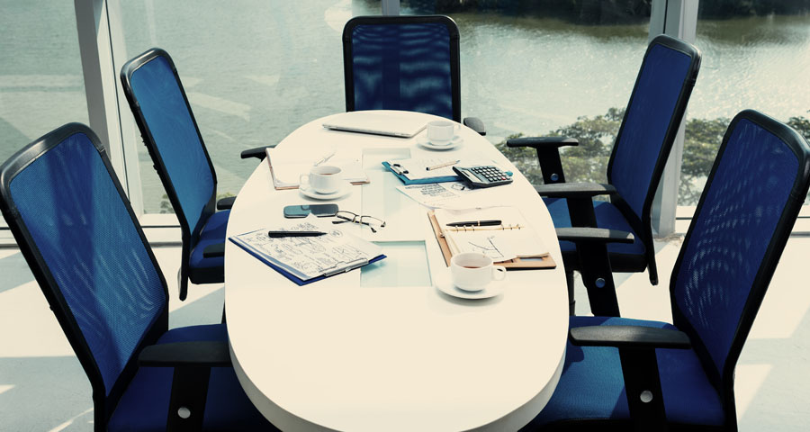 empty conference table with notebooks, phone, coffee cups