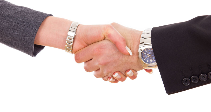 close up of business man and woman shaking hands