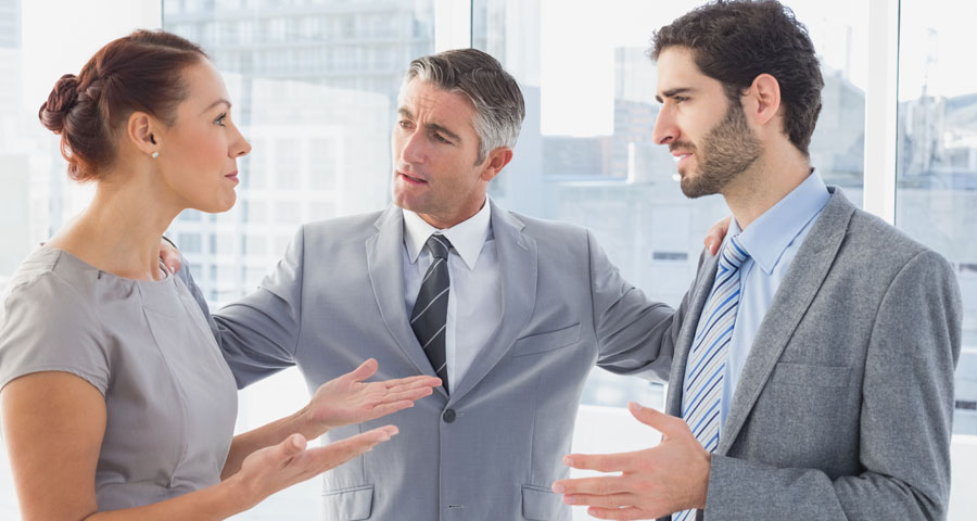 concerned businessman standing between business woman and man