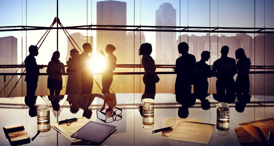 Silhouette of businessmen and women in conference room with setting sun and skyline background