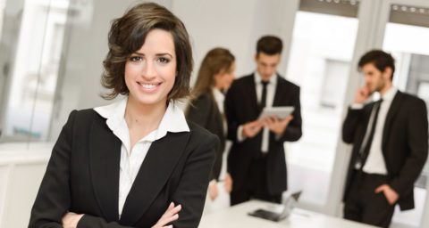 business woman in forground with business colleagues in background