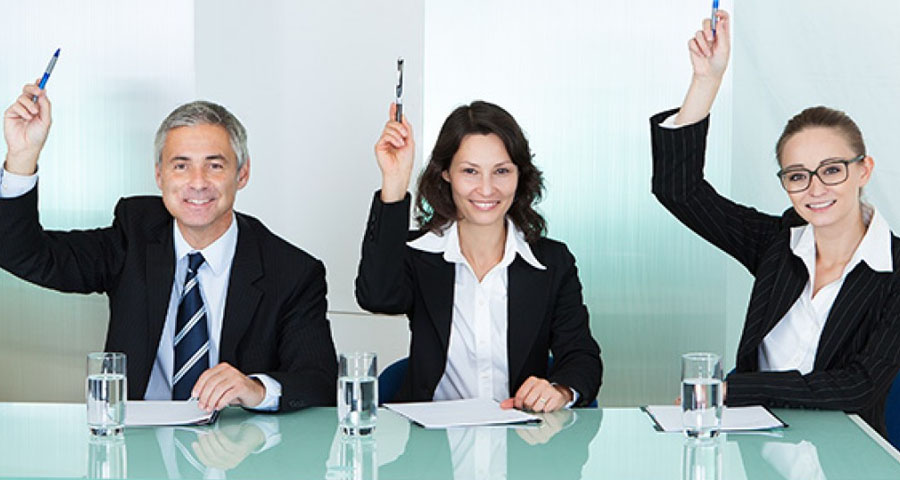 business people at table with hands raised