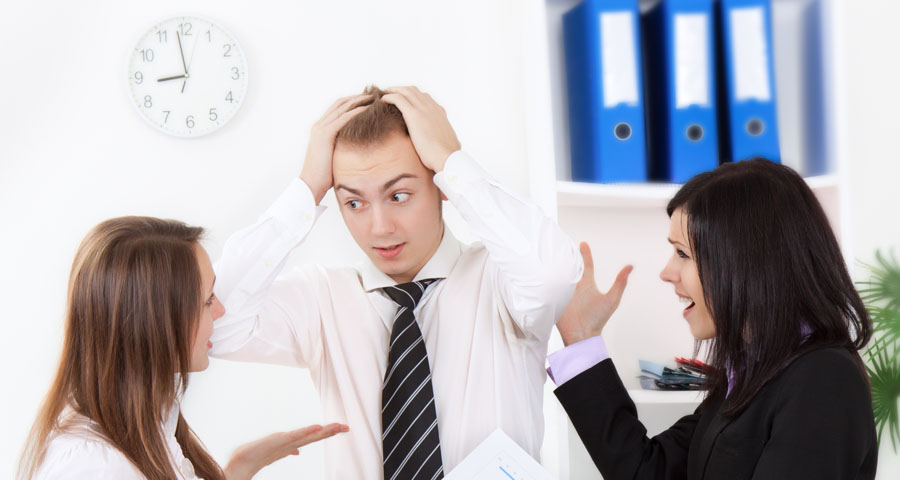 business man pulling hair as he listens to women coworkers vent