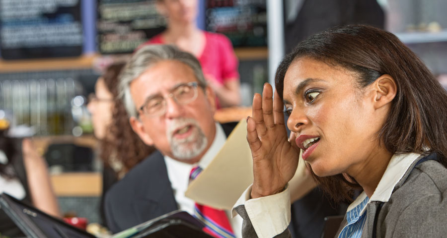 business woman trying to ignore business man shoving papers in her face