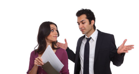 business man shrugging over the sholder of female coworker