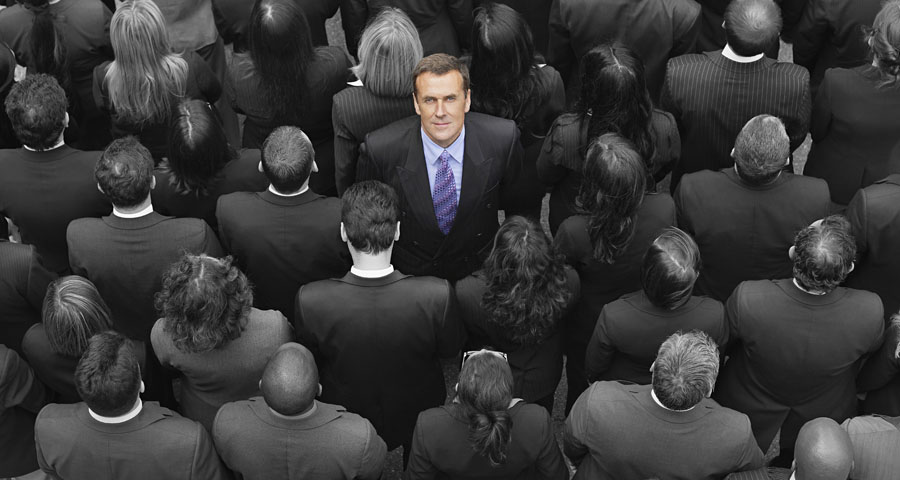 business man looking up in a crowd of business people with backs turned