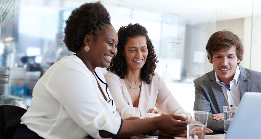 smiling business women and man in front of computer