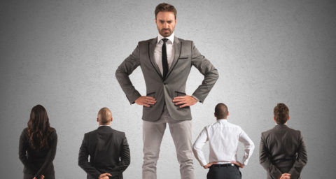 giant business man standing in front of other business men and women looking displeased
