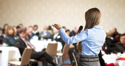 business woman speaking to a group of business people