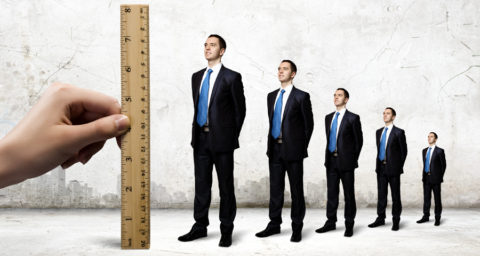 ruler measuring up 3 business men