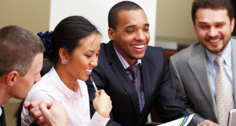 business men and women laughing during meeting