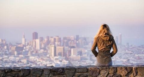 woman sitting on stone wall staring at city scape below