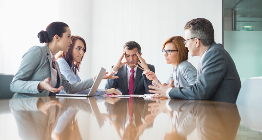 business man holding head as others around him argue in meeting