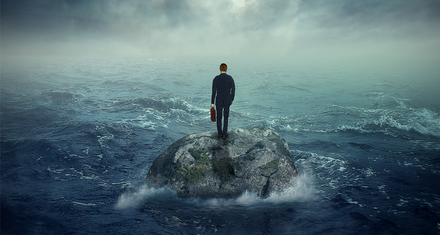 business man standing alone on a rock in the middle of the ocean