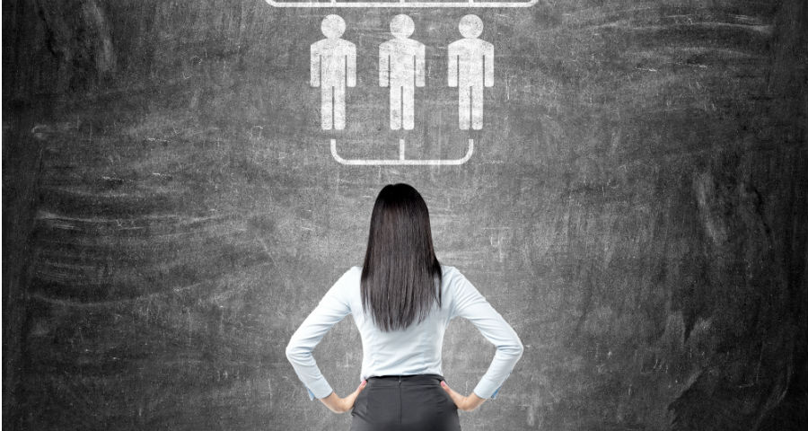 business woman standing in front of a chalkboard illustration of delegating