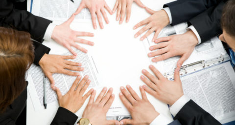 business people's hands laid flat on a table to form a circle