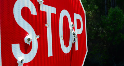 stop sign with bullet holes in it